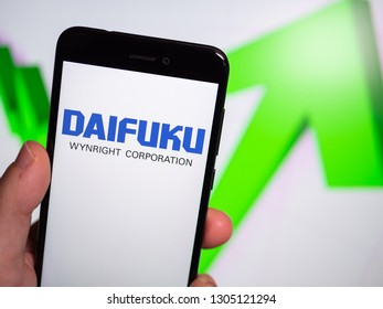 Murcia, Spain; Jan 31, 2019: Daifuku logo in phone with rises graphic on background. First person view