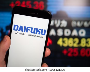 Murcia, Spain; Jan 31, 2019: Daifuku logo in phone with Tokyo stock exchange screen on background. First person view