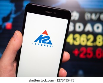 Murcia, Spain; Jan 8, 2019: K2 Sports logo in phone with stock exchange screen on background. First person view