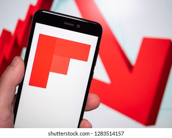 Murcia, Spain; Jan 8, 2019: Flipboard icon in phone with losses graphic on background. First person view