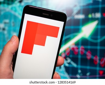 Murcia, Spain; Jan 8, 2019: Flipboard icon in phone with earnings graphic on background. Flipboard is a news aggregator and social network aggregation company