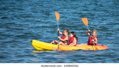 Murcia, Spain, July 17, 2019: Happy children playing on the beach in Summer. Childhood at summer camp. Aquatic activities and sports with childs. Vacation with friends. Kid or kids kayaking.