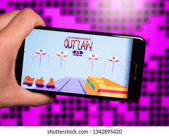Murcia, Spain; Mar 17, 2019: Hypnospace Outlaw logo in phone with computer screen on background. First person view