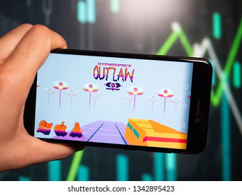 Murcia, Spain; Mar 17, 2019: Hand holding phone with Hypnospace Outlaw logo displayed in it with fluctuating graphic on background. First person view