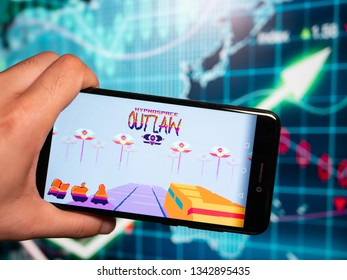 Murcia, Spain; Mar 17, 2019: Hypnospace Outlaw logo in phone with earnings graphic on background. Hypnospace Outlaw is an Internet and OS Simulation game set in an alternate-reality