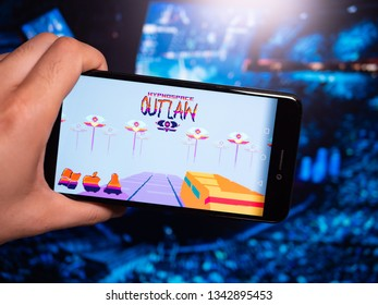 Murcia, Spain; Mar 17, 2019: Hypnospace Outlaw logo in phone with esports tournament on background. Hypnospace Outlaw is an Internet and OS Simulation game set in an alternate-reality