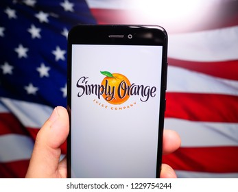 Murcia, Spain; Nov 13, 2018: Simply Orange Juice Company logo in phone with United States flag on background. Simply Orange Juice Company makes a number of not-from-concentrate orange juices