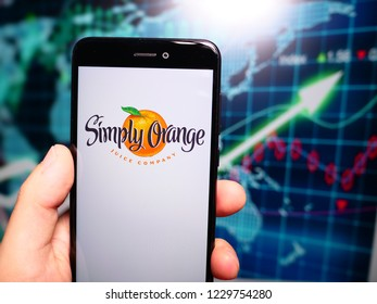 Murcia, Spain; Nov 13, 2018: Simply Orange Juice Company logo in phone with earnings graphic on background. Simply Orange Juice Company makes a number of not-from-concentrate orange juices