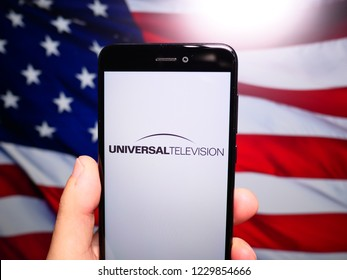 Murcia, Spain; Nov 13, 2018: Universal Television logo in phone with United States flag on background. Universal Television is the television production subsidiary of the NBCUniversal Television Group