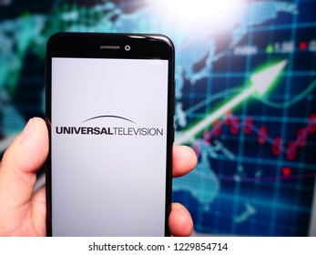 Murcia, Spain; Nov 13, 2018: Universal Television logo in phone with earnings graphic on background. Universal Television is the television production subsidiary of the NBCUniversal Television Group