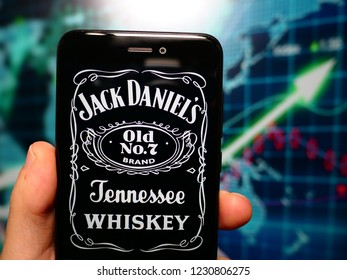 Murcia, Spain; Nov 14, 2018: Jack Daniel's logo in phone with earnings graphic on background. Jack Daniel's is a brand of Tennessee whiskey and the top selling American whiskey in the world
