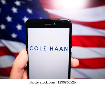 Murcia, Spain; Nov 15, 2018: Cole Haan logo in phone with United States flag on background. Cole Haan is a global men's and women's footwear and accessories brand