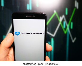 Murcia, Spain; Nov 15, 2018: Hand holding phone with Colgate Palmolive Company logo displayed in it with fluctuating graphic on background. First person view