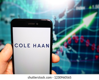 Murcia, Spain; Nov 15, 2018: Cole Haan logo in phone with earnings graphic on background. Cole Haan is a global men's and women's footwear and accessories brand