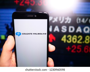 Murcia, Spain; Nov 15, 2018: Colgate Palmolive logo in phone with New York stock exchange (NYSE) screen on background. First person view
