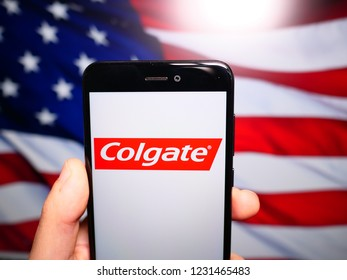 Murcia, Spain; Nov 15, 2018: Colgate logo in phone with United States flag on background. Colgate is an umbrella brand principally used to purchase oral hygiene products
