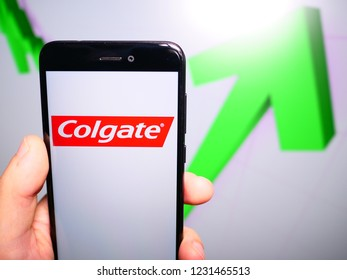 Murcia, Spain; Nov 15, 2018: Colgate logo in phone with rises graphic on background. First person view