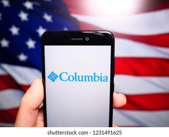 Murcia, Spain; Nov 15, 2018: Columbia Sportswear logo in phone with United States flag on background. Columbia Sportswear is an American company that manufactures and distributes outerwear, footwear