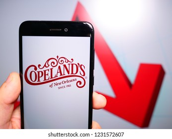 Murcia, Spain; Nov 15, 2018: Copeland's logo in phone with losses graphic on background. First person view