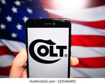 Murcia, Spain; Nov 15,2018: Colt Manufacturing logo in phone with United States flag on background, Colt's is an American firearms manufacturer
