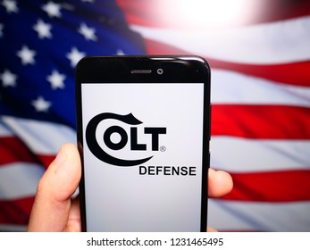 Murcia, Spain; Nov 15,2018: Colt Defense logo in phone with United States flag on background, Colt's is an American firearms manufacturer