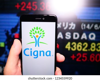 Murcia, Spain; Nov 19, 2018: Cigna logo in phone with New York stock exchange (NYSE) screen on background. First person view