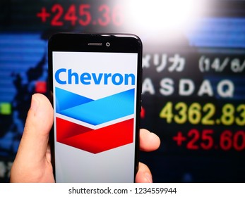 Murcia, Spain; Nov 19, 2018: Chevron Corporation logo in phone with New York stock exchange (NYSE) screen on background. First person view