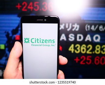 Murcia, Spain; Nov 19, 2018: Citizens Financial Group logo in phone with New York stock exchange (NYSE) screen on background. First person view