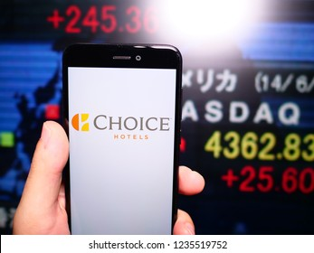 Murcia, Spain; Nov 19, 2018: Choice Hotels logo in phone with New York stock exchange (NYSE) screen on background. First person view