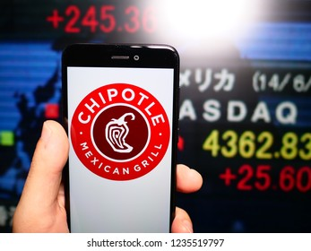 Murcia, Spain; Nov 19, 2018: Chipotle Mexican Grill logo in phone with New York stock exchange (NYSE) screen on background. First person view
