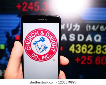 Murcia, Spain; Nov 19, 2018: Church & Dwight logo in phone with New York stock exchange (NYSE) screen on background. First person view