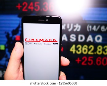 Murcia, Spain; Nov 19, 2018: Cinemark Theatres logo in phone with New York stock exchange (NYSE) screen on background. First person view