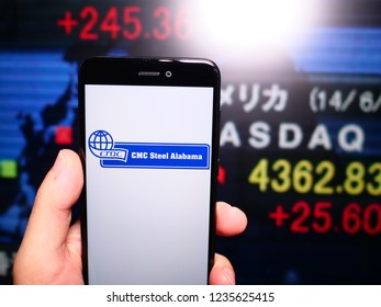 Murcia, Spain; Nov 19, 2018: Commercial Metals Company logo in phone with New York stock exchange (NYSE) screen on background. First person view