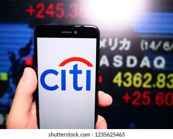 Murcia, Spain; Nov 19, 2018: Citigroup (Citi) logo in phone with New York stock exchange (NYSE) screen on background. First person view