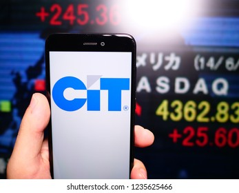 Murcia, Spain; Nov 19, 2018: CIT Group logo in phone with New York stock exchange (NYSE) screen on background. First person view
