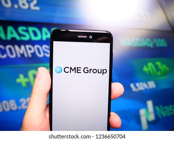 Murcia, Spain; Nov 19, 2018: CME Group logo in phone with Nasdaq index screen on background. First person view