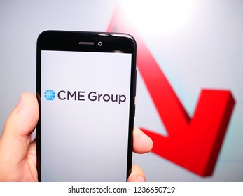 Murcia, Spain; Nov 19, 2018: CME Group logo in phone with losses graphic on background. First person view