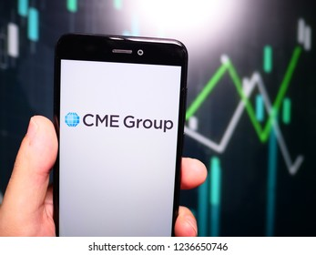 Murcia, Spain; Nov 19, 2018: Hand holding phone with CME Group logo in phone with fluctuating graphic on background. First person view