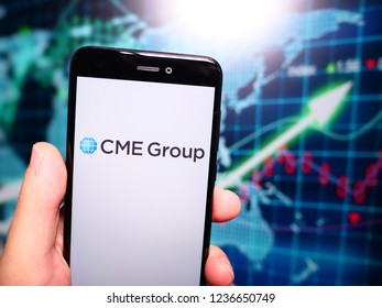Murcia, Spain; Nov 19, 2018: CMe Group logo in phone with earnings graphic on background. CME Group is an American financial market company operating