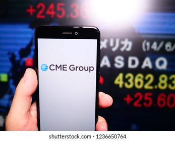 Murcia, Spain; Nov 19, 2018: CME Group logo in phone with stock exchange screen on background. First person view