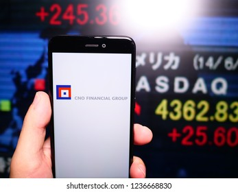 Murcia, Spain; Nov 19, 2018: CNO Financial Group logo in phone with New York stock exchange (NYSE) screen on background. First person view