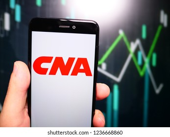 Murcia, Spain; Nov 19, 2018: Hand holding phone with CNA Financial Corporation logo displayed in it with fluctuating graphic on background. First person view