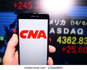 Murcia, Spain; Nov 19, 2018: CNA Financial Corporation logo in phone with New York stock exchange (NYSE) screen on background. First person view