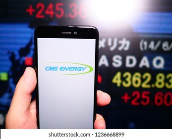 Murcia, Spain; Nov 19, 2018: CMS Energy logo in phone with New York stock exchange (NYSE) screen on background. First person view