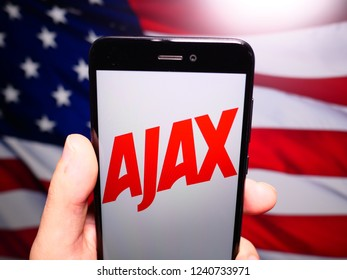 Murcia, Spain; Nov 21, 2018: Ajax logo in phone with United States flag on background. Ajax is a brand of cleaning products of Colgate-Palmolive