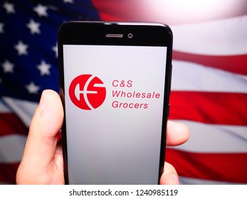 Murcia, Spain; Nov 21, 2018: C&S Wholesale Grocers logo in phone with United States flag on background. C&S Wholesale Grocers is an American wholesale distribution of food and grocery store