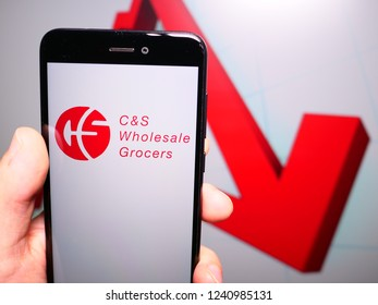 Murcia, Spain; Nov 21, 2018: C&S Wholesale Grocers logo in phone with losses graphic on background. First person view