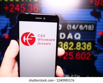 Murcia, Spain; Nov 21, 2018: C&S Wholesale Grocers logo in phone with stock exchange screen on background. First person view