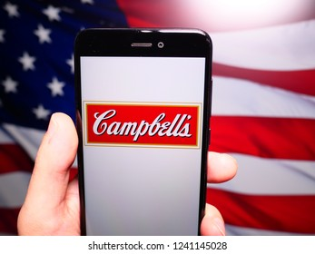 Murcia, Spain; Nov 21, 2018: Campbell Soup Company logo in phone with United States flag on background. Campbell Soup Company, also known as just Campbell's, is an American producer of canned soups