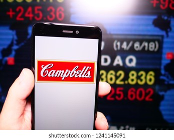 Murcia, Spain; Nov 21, 2018: Campbell Soup Company logo in phone with New York stock exchange (NYSE) screen on background. First person view